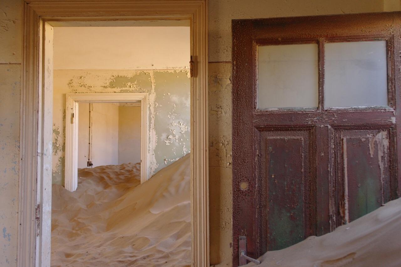 Verlaten woning vol met zand in Kolmanskop, Namibië.